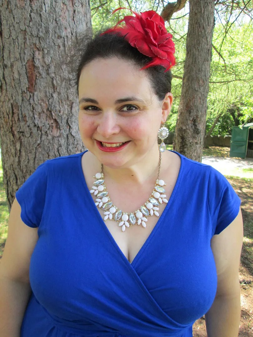 plus size red, white, and blue outfit - blue wrap dress, white necklace, red hair flower