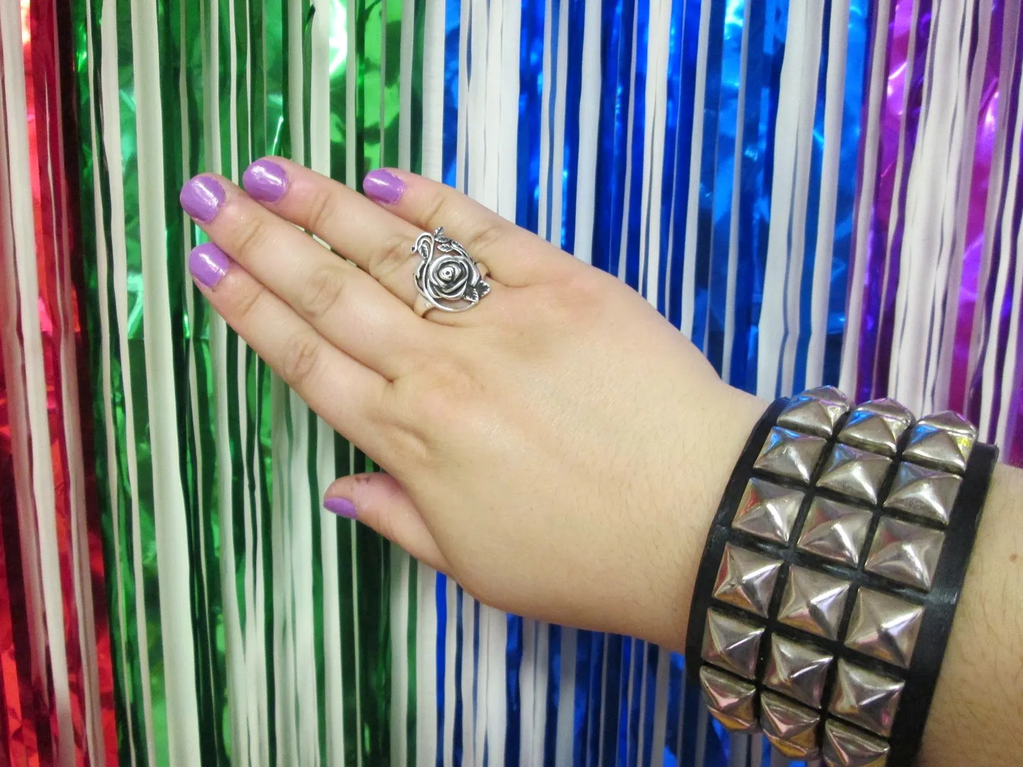 hand with studded wristband, purple nail polish, and rose ring