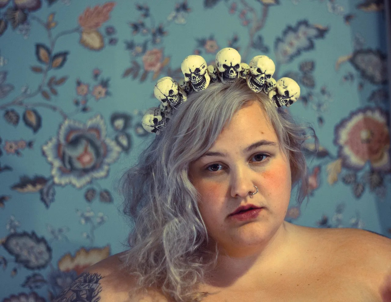 plus size woman with pastel silver hair wearing white skull crown headband