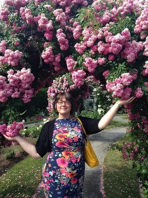 plus size outfit with blue floral dress and black jacket, next to pink flowering trees