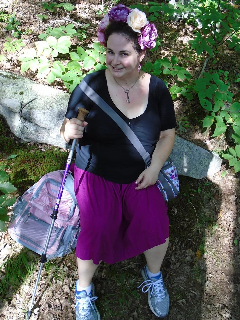 woman sitting on rock with hiking pole, wearing flower crown