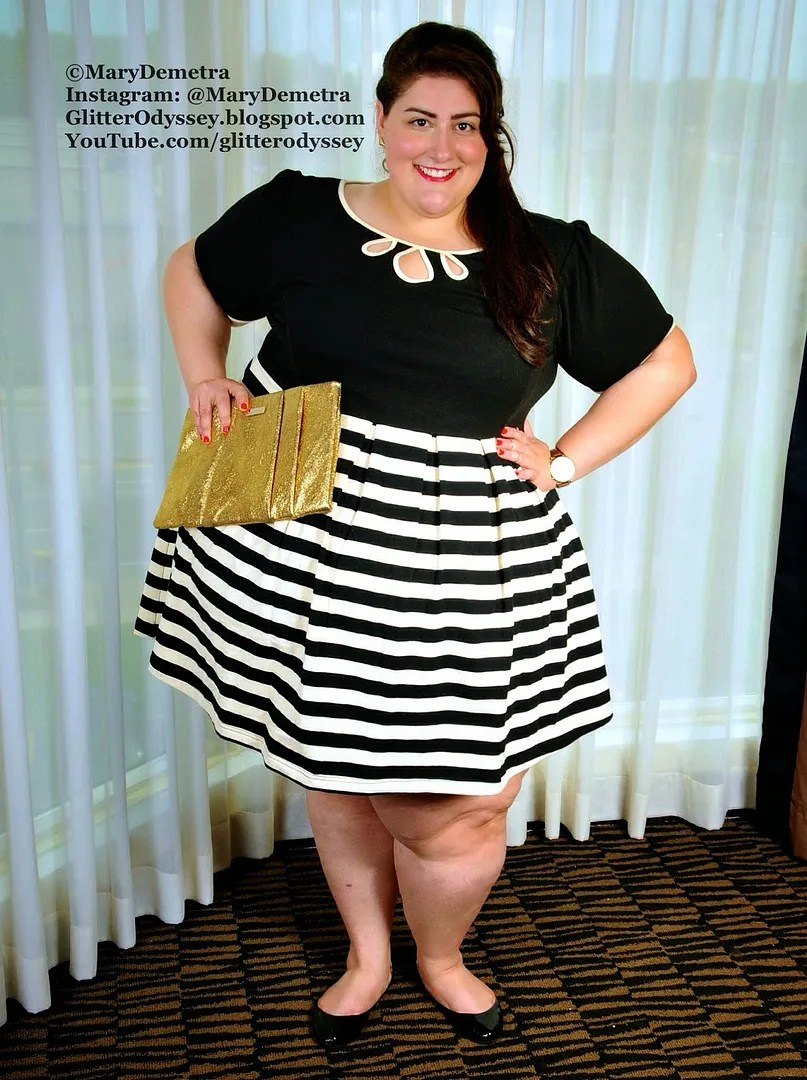 plus size dress with black top and black and white striped skirt, gold clutch