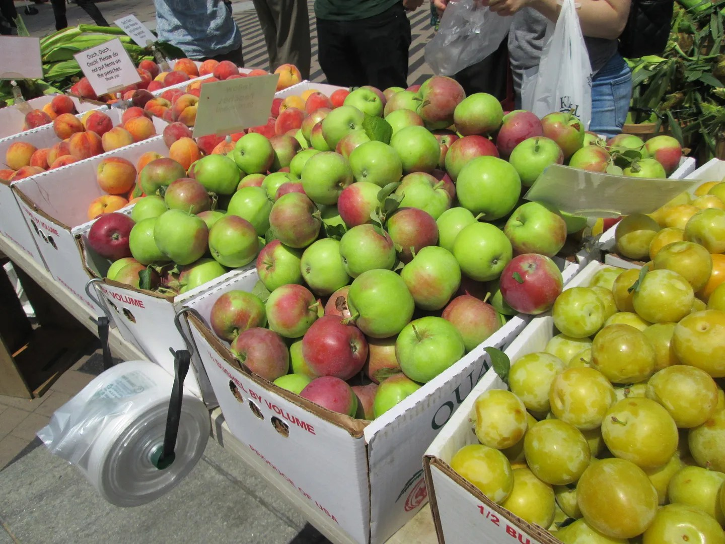 boxes of apples, peaches, and yellow plums at the farmers market