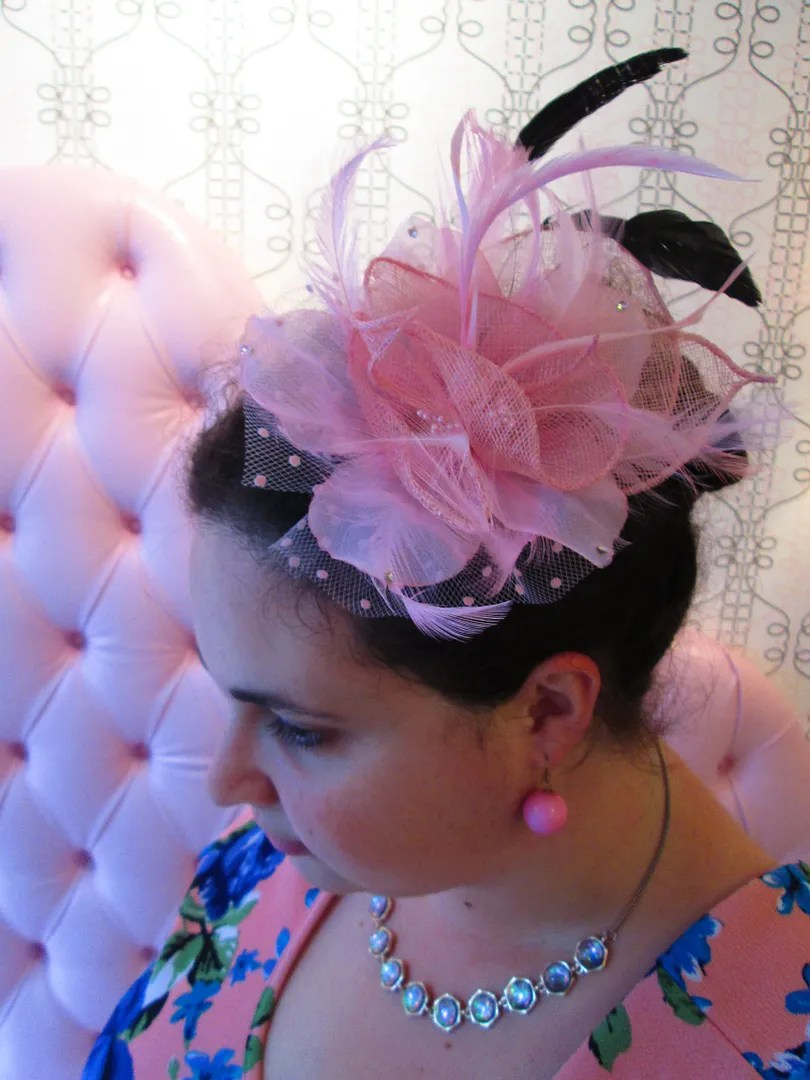 close-up of pink feather and floral fascinator
