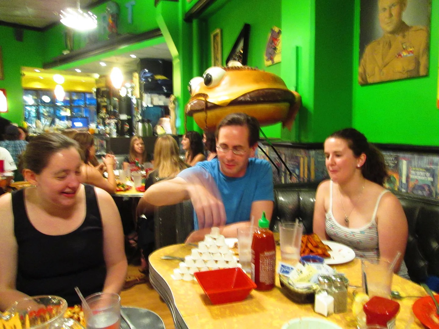 giant creepy hamburger statue in back of people eating dinner