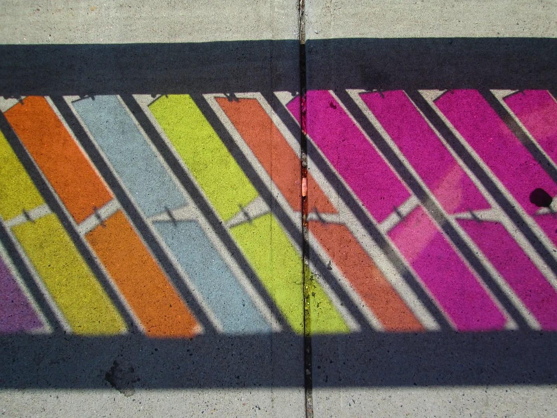 rainbow reflections on sidewalk