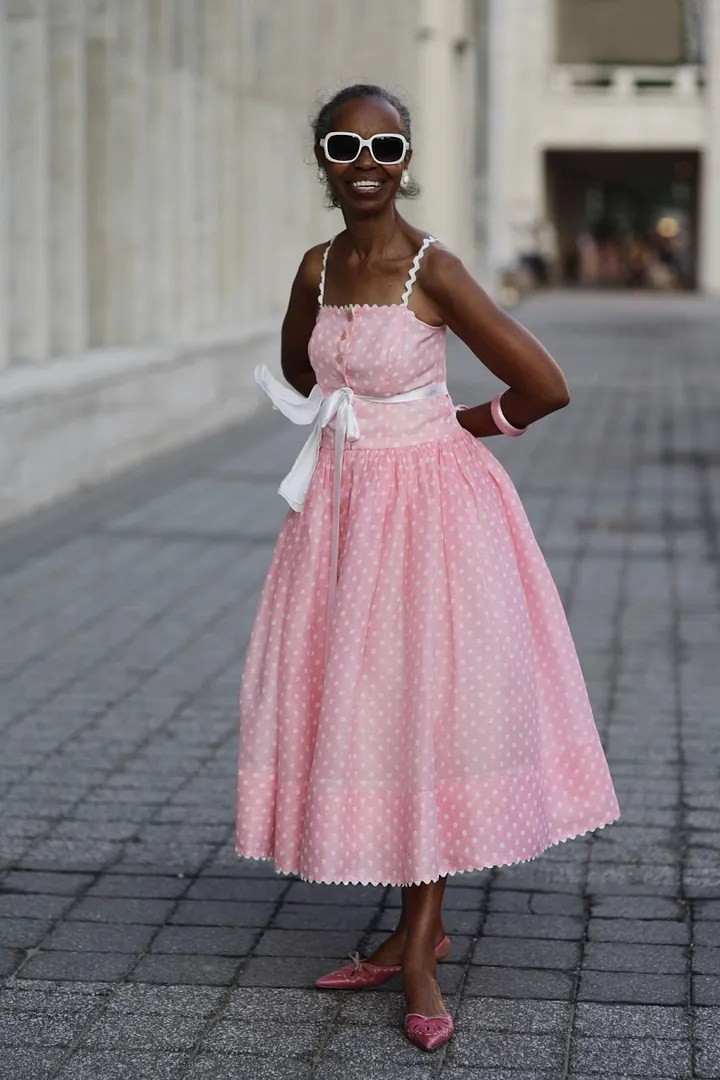 advanced style older woman wearing light pink polka dot retro dress