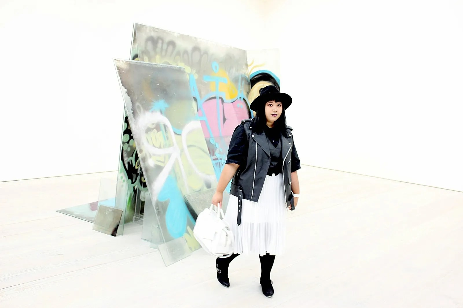 plus size punk outfit with black leather vest, black top, white chiffon skirt, black hat