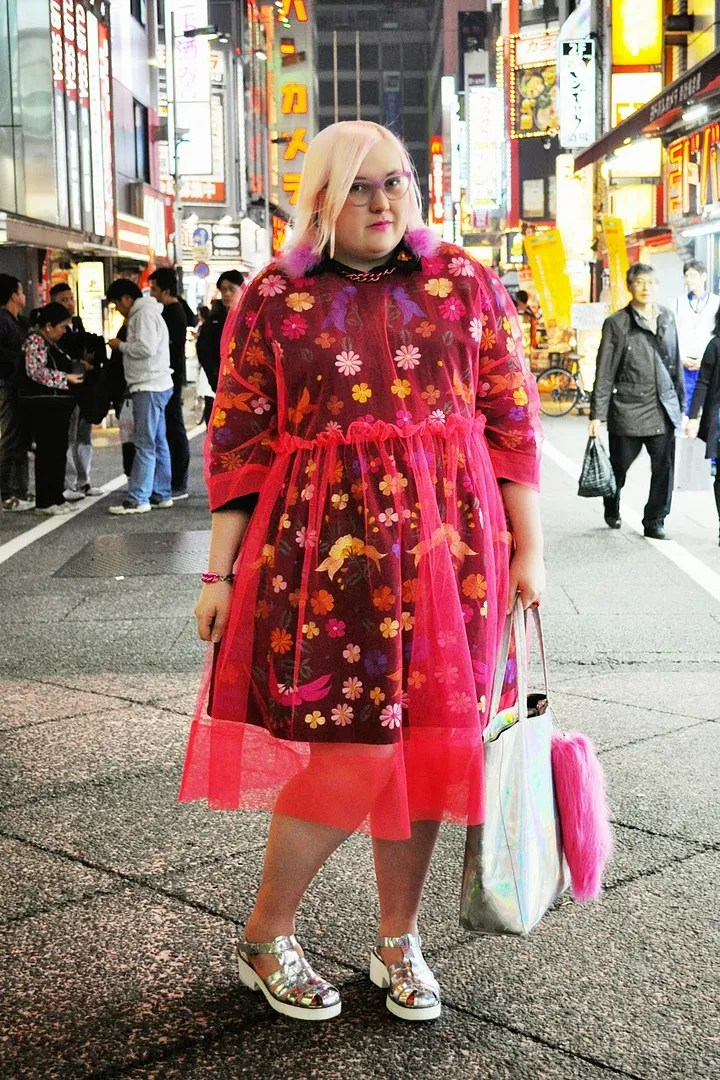 plus size harajuku outfit with sheer red dress over floral embroidered dress, holographic shoes and purse, and pink fuzzy earrings