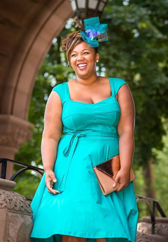 plus size outfit with turquoise dress and turquoise, purple, and peacock fascinator