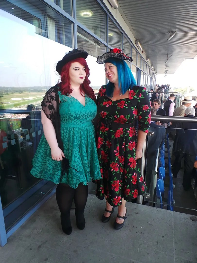 two plus size women dressed up for the races with floral and lace dresses and fascinators