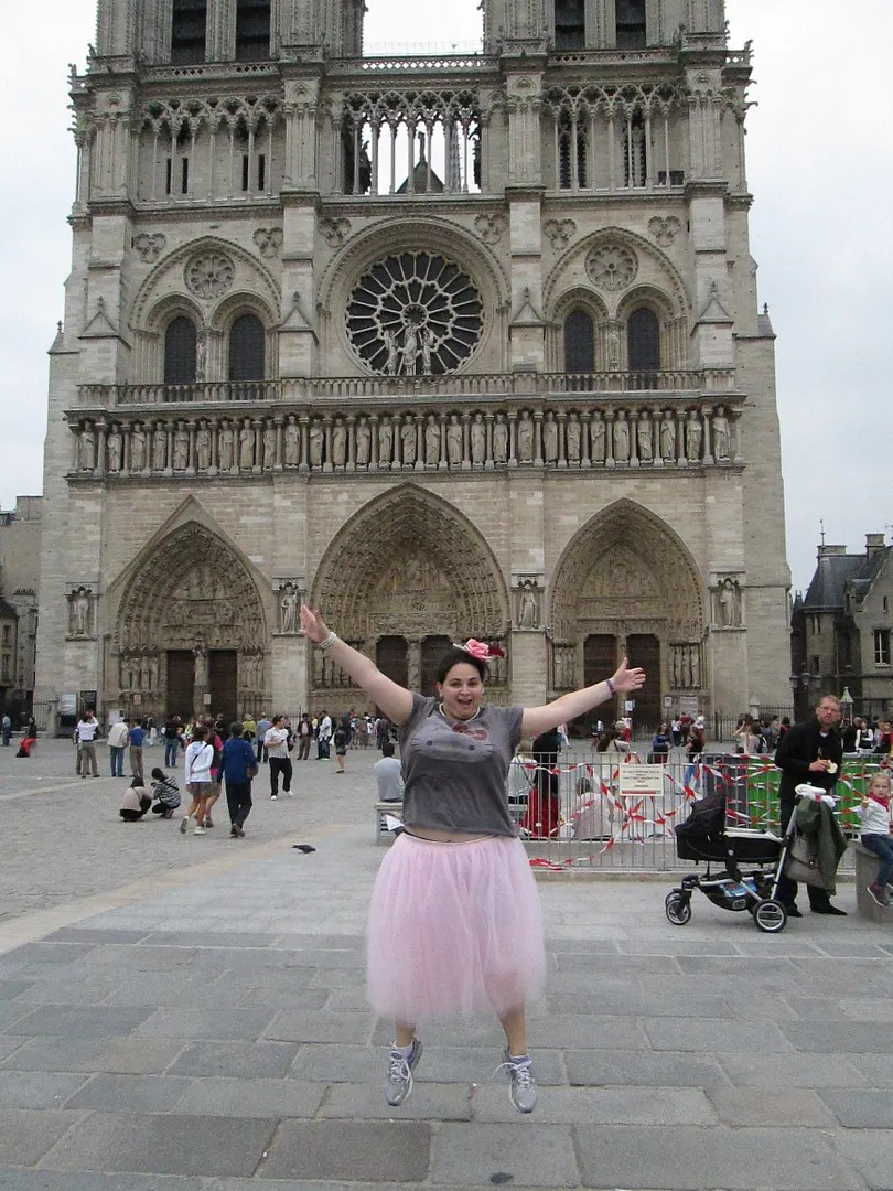 woman in pink tutu jumping in front of the notre dame cathedral