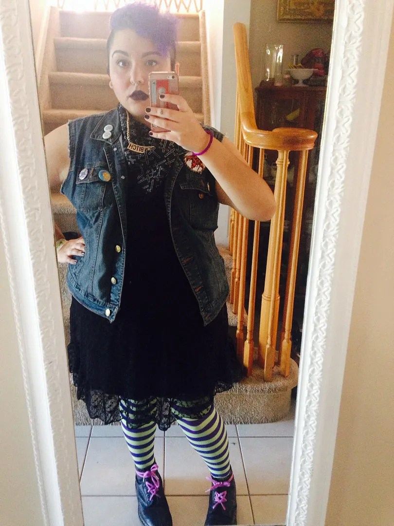 plus size spooky outfit with black lace dress, striped tights, and denim vest
