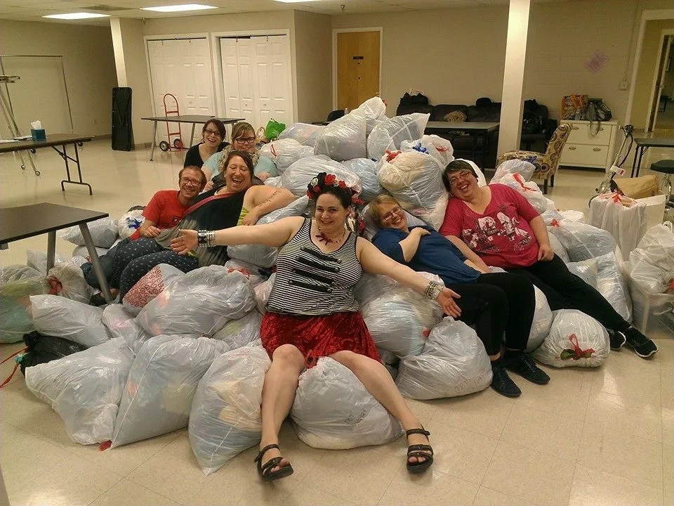 group of volunteers sitting on pile of bagged clothing donations