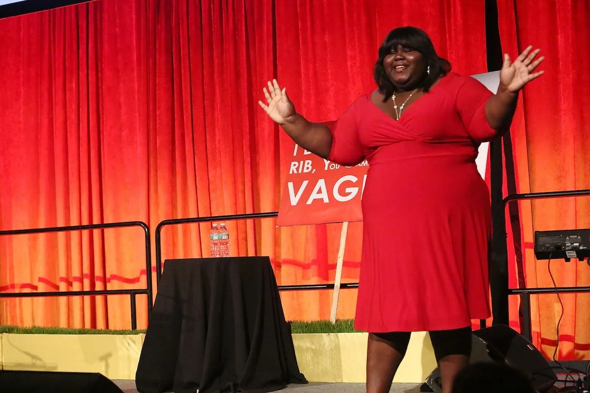 gabourey sidibe giving a speech, wearing a red wrap dress