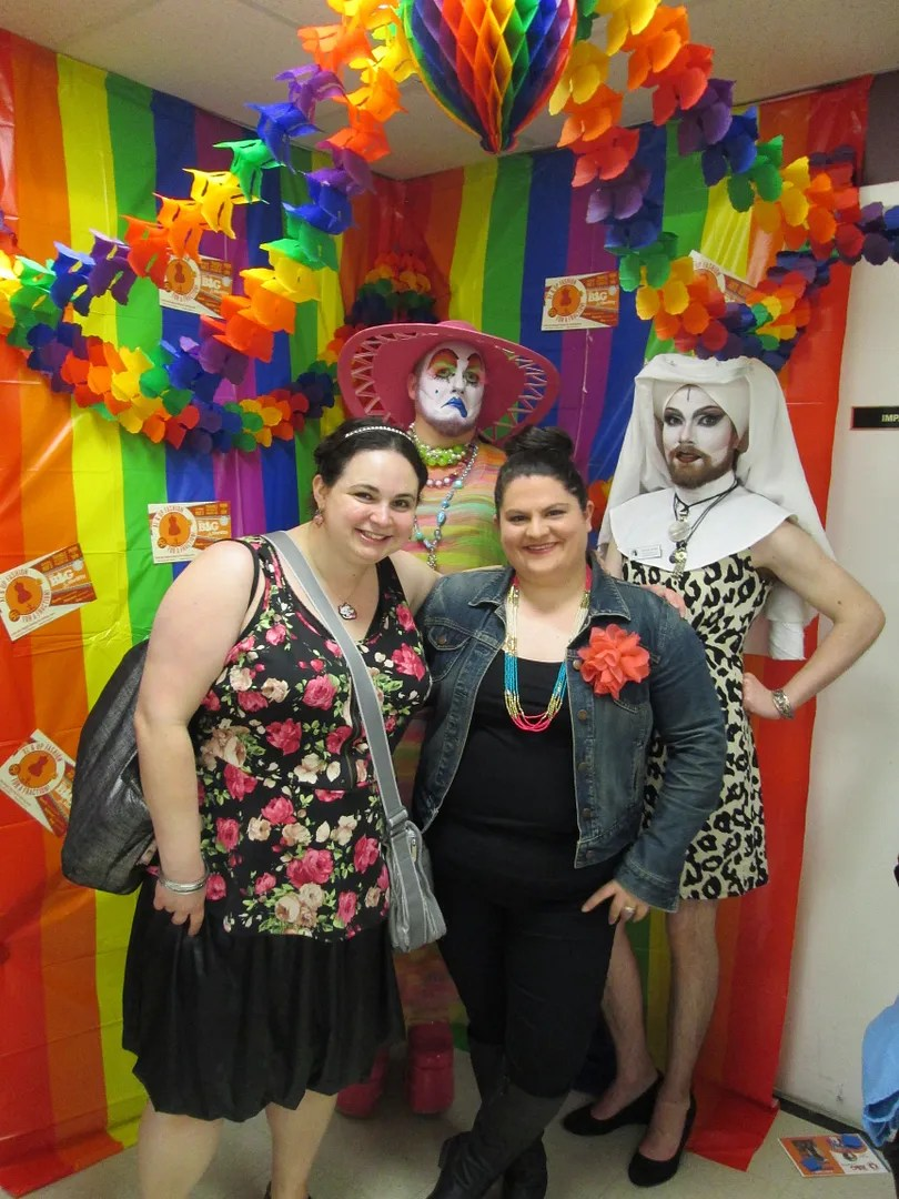 two women with queer nuns in rainbow photobooth