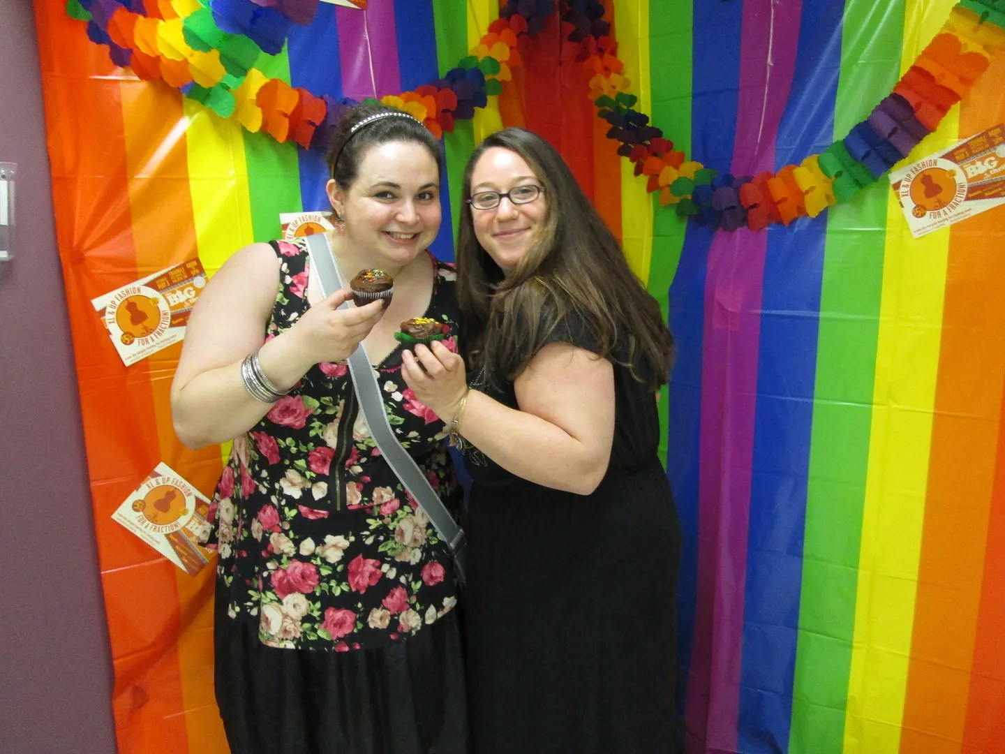 two women holding cupcakes in rainbow photobooth
