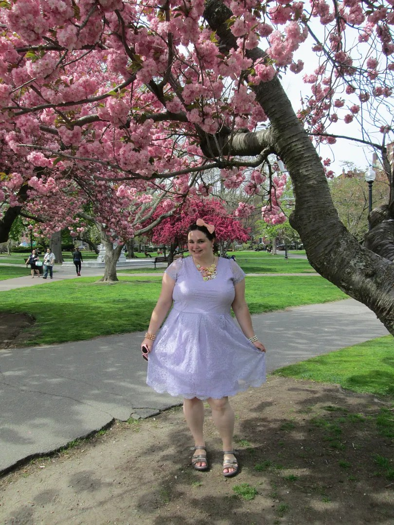 woman in lavender lace dress and peach hair bow in front of pink cherry trees