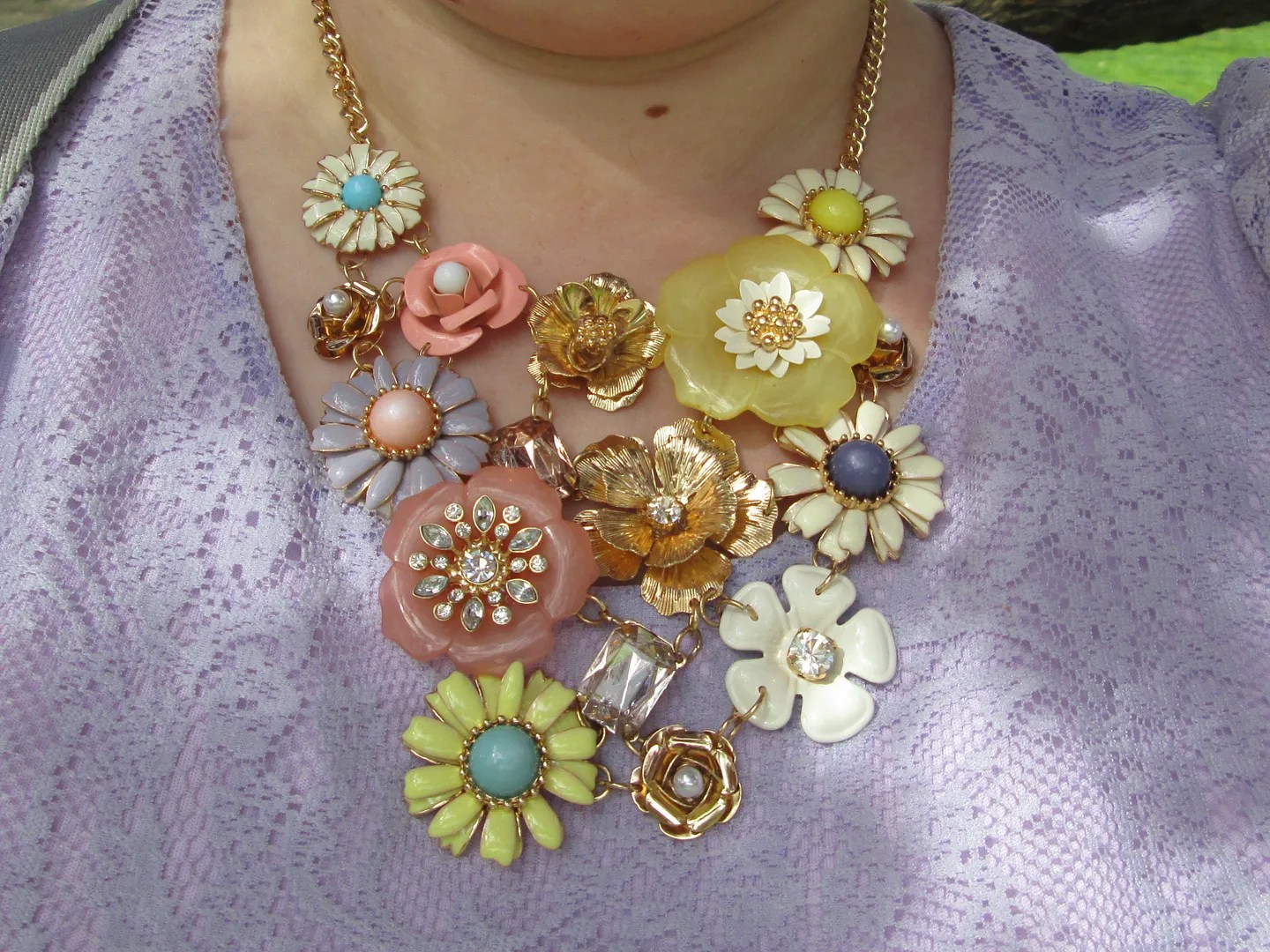 close-up of pastel floral and gold statement necklace