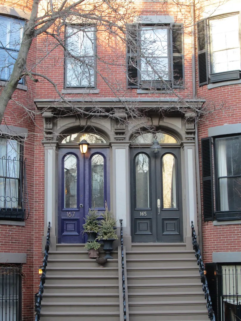 brownstone house with purple and black doors and fancy scrollwork railings
