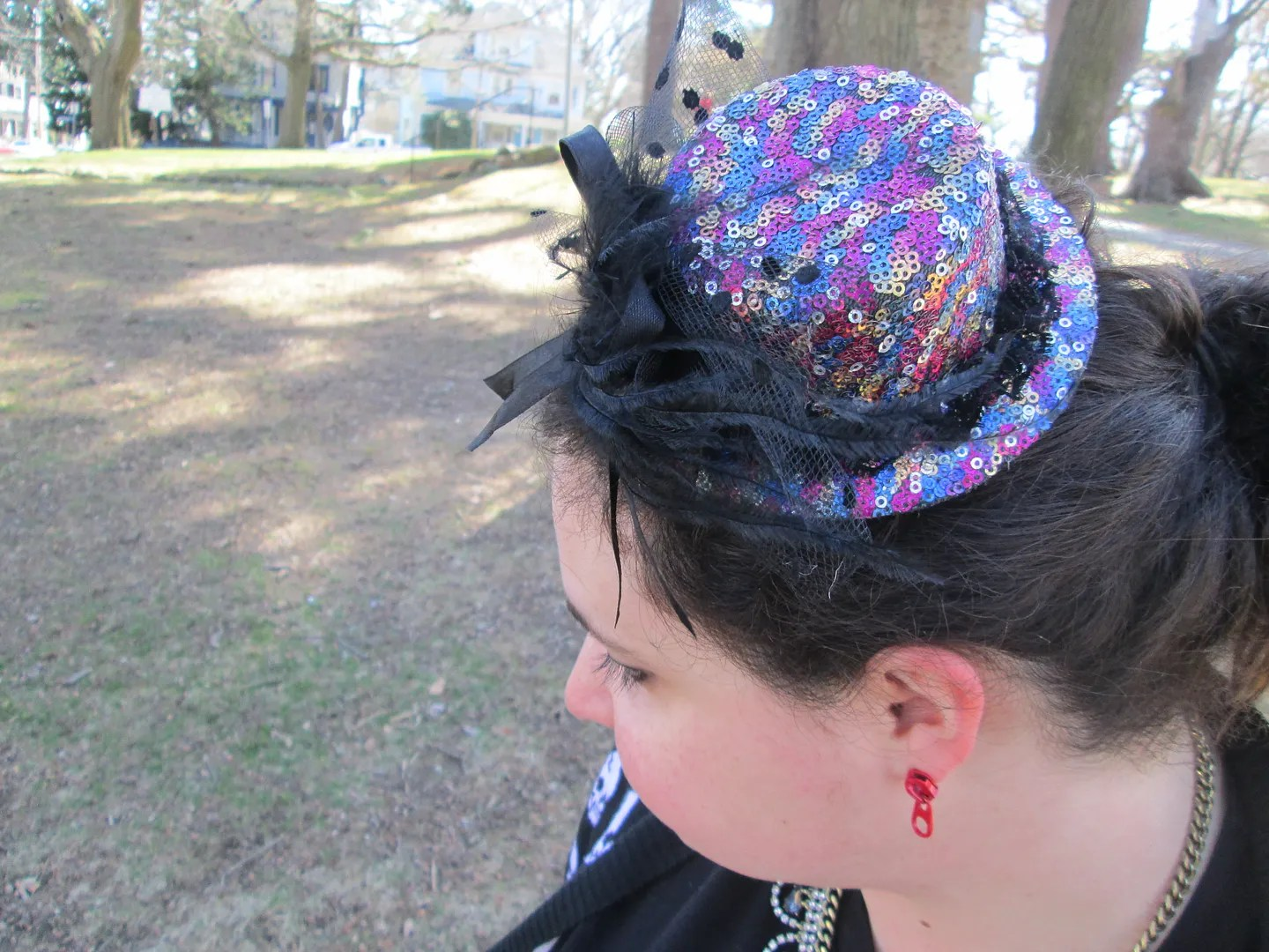 multicolored sequined tiny hat fascinator and red zipper pull earrings