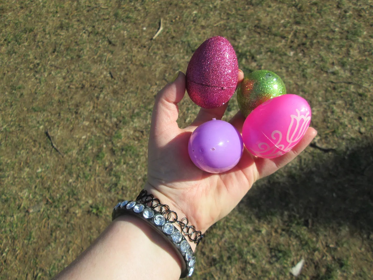 hand holding pink, green, and purple sparkly easter eggs
