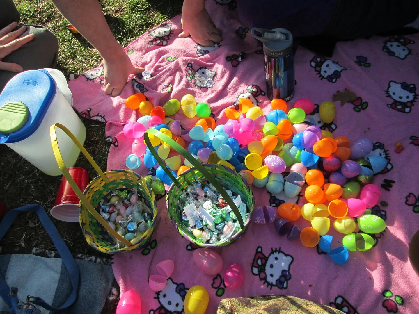 pile of colorful easter eggs on pink hello kitty picnic blanket