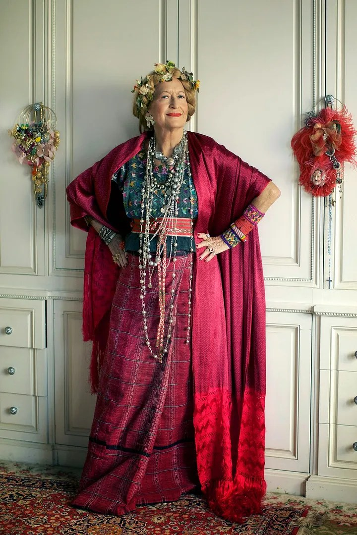 older woman wearing glamorous red and blue outfit with a lot of jewelry