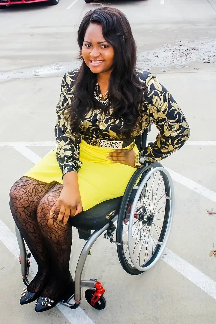 woman in wheelchair wearing black and gold top and bright yellow pencil skirt