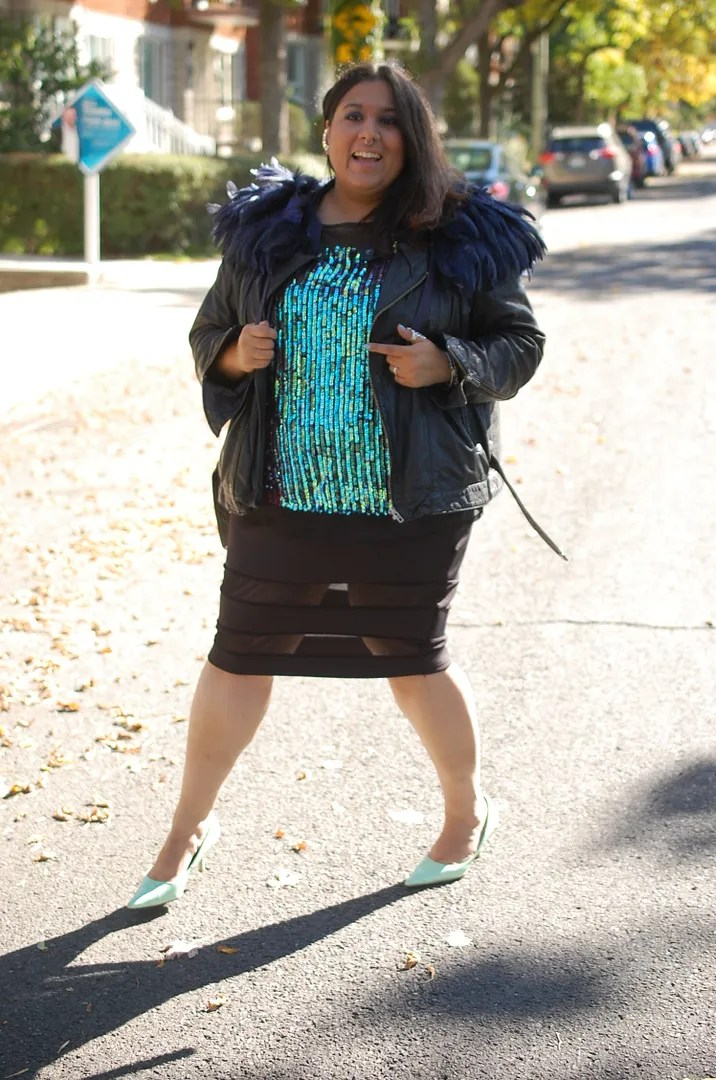 plus size glam outfit with turquoise sequin top, black sheer bandage skirt, and black jacket with feathered epaullettes