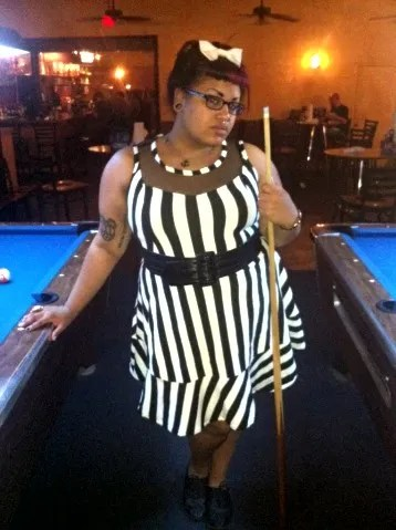 woman standing with pool cue wearing black and white vertical striped dress and white bow