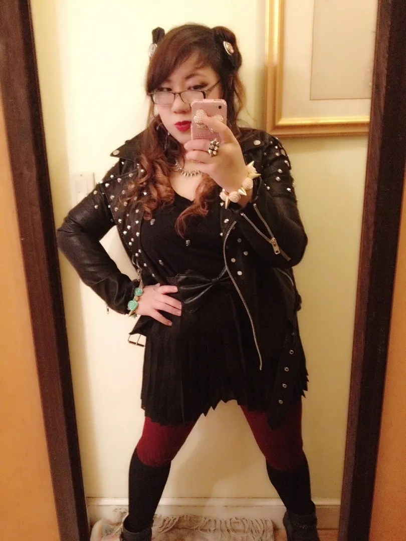 woman wearing mostly black punk outfit with studded leather jacket