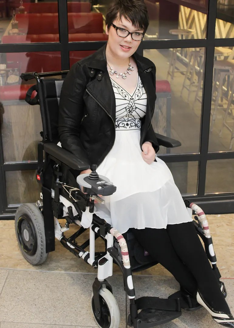 plus size outfit in wheelchair with white flapper dress and rhinestone accessories