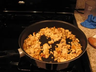 Minimally golden tempeh in the pan, some less-than-golden areas can be seen