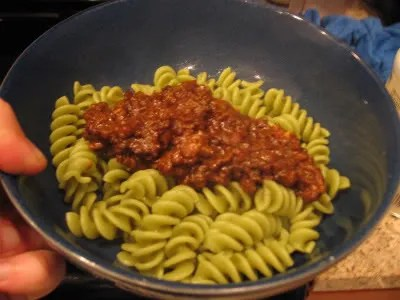 A relatively small pile of tempeh and sauce sits on top of the noodles in the bowl