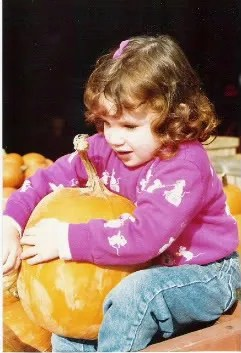 Me at about age 2, sitting in a pumpkin patch hugging the pumpkin