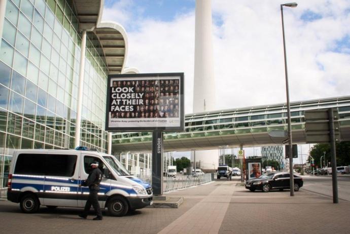 Плакат з фотографіями бійців та волонтерів було розміщено біля входу до Арени, де проходив саміт G20