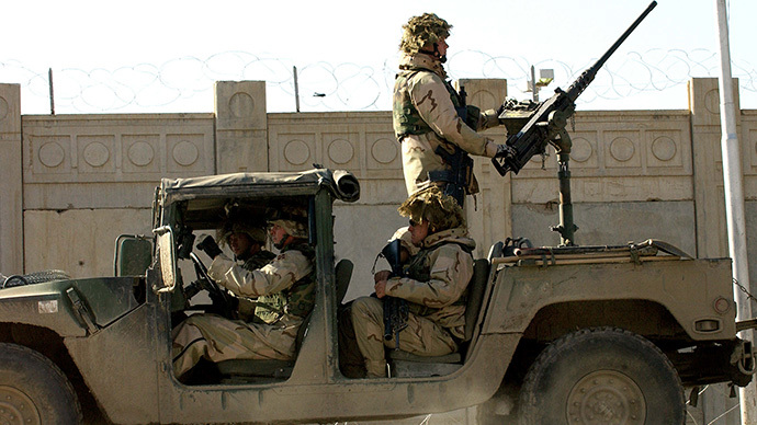 US soldiers from the 1st Battalion, 22nd Regiment of the 4th Infantry Division, ride on a military vehicle as they leave their base on a mission in Tikrit, 180 Kilometers north of Iraqi capital Baghdad, 30 December 2003.