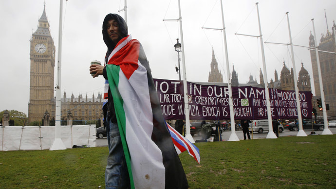 A pro-Palestine supporter wears a Palestinian and Union flag outside the Houses of Parliament in London October 13, 2014.  (Reuters/Luke MacGregor)