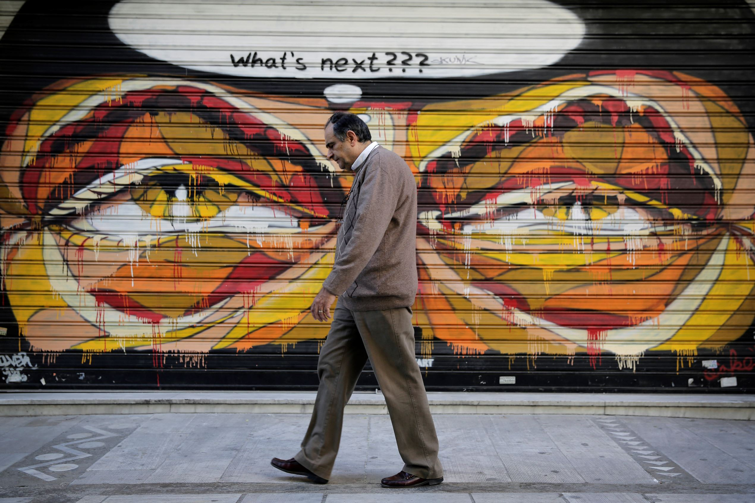 In this photo made on Tuesday, April 29, 2015, a Greek man walks past a graffiti in central Athens. Wednesday May 6 marks five years since Greece voted in its first bailout deal in the face of violent popular protests that left three dead. The day was followed by years of turmoil in which the country tried to overhaul its economy in the midst of a downturn matched in depth and length only by the Great Depression.