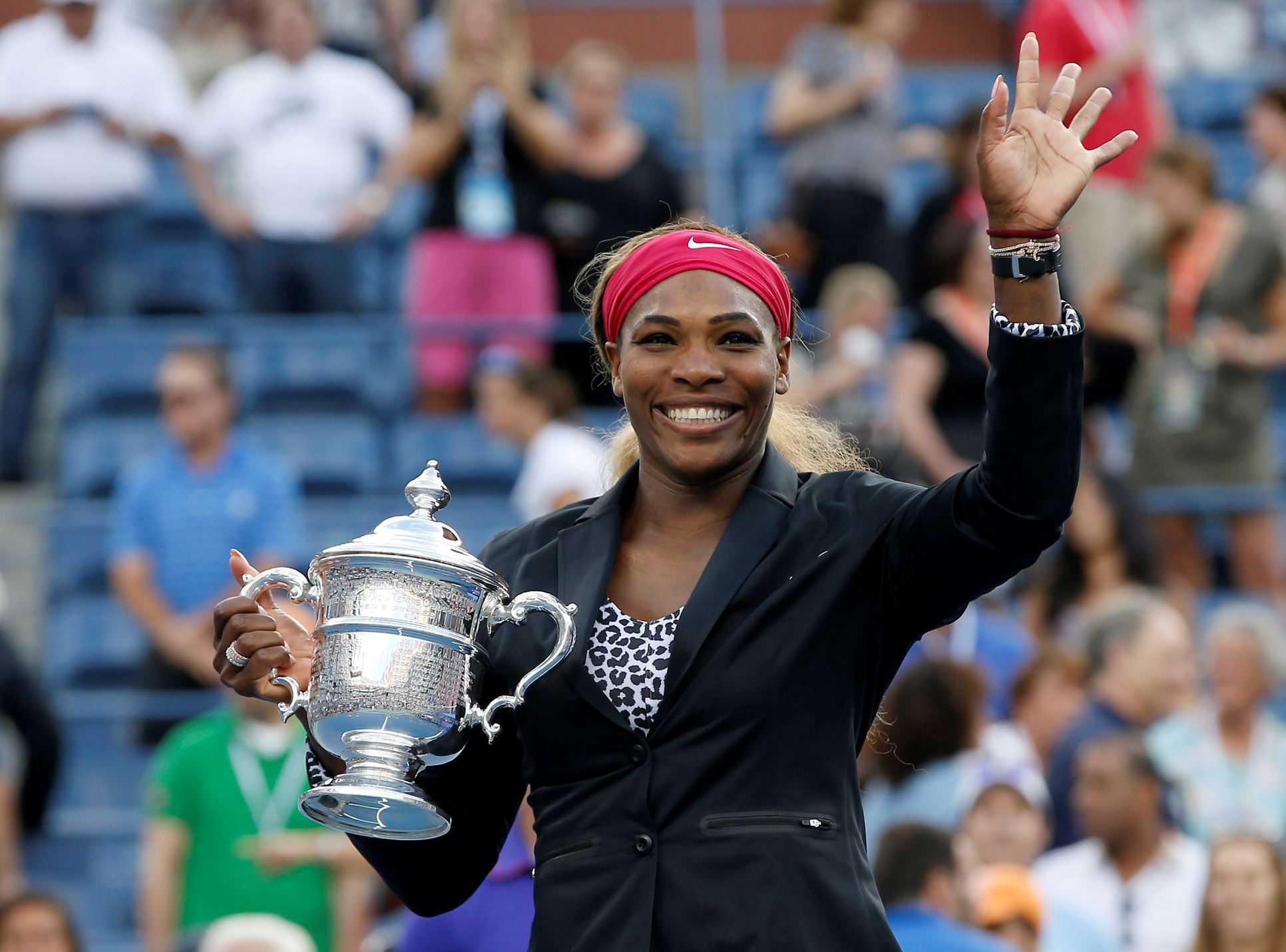 Serena Williams of the U.S. holds her trophy and waves to the crowd after defeating Caroline Wozniacki of Denmark in their women's singles finals match at the 2014 U.S. Open tennis tournament in New York City on Sunday.
