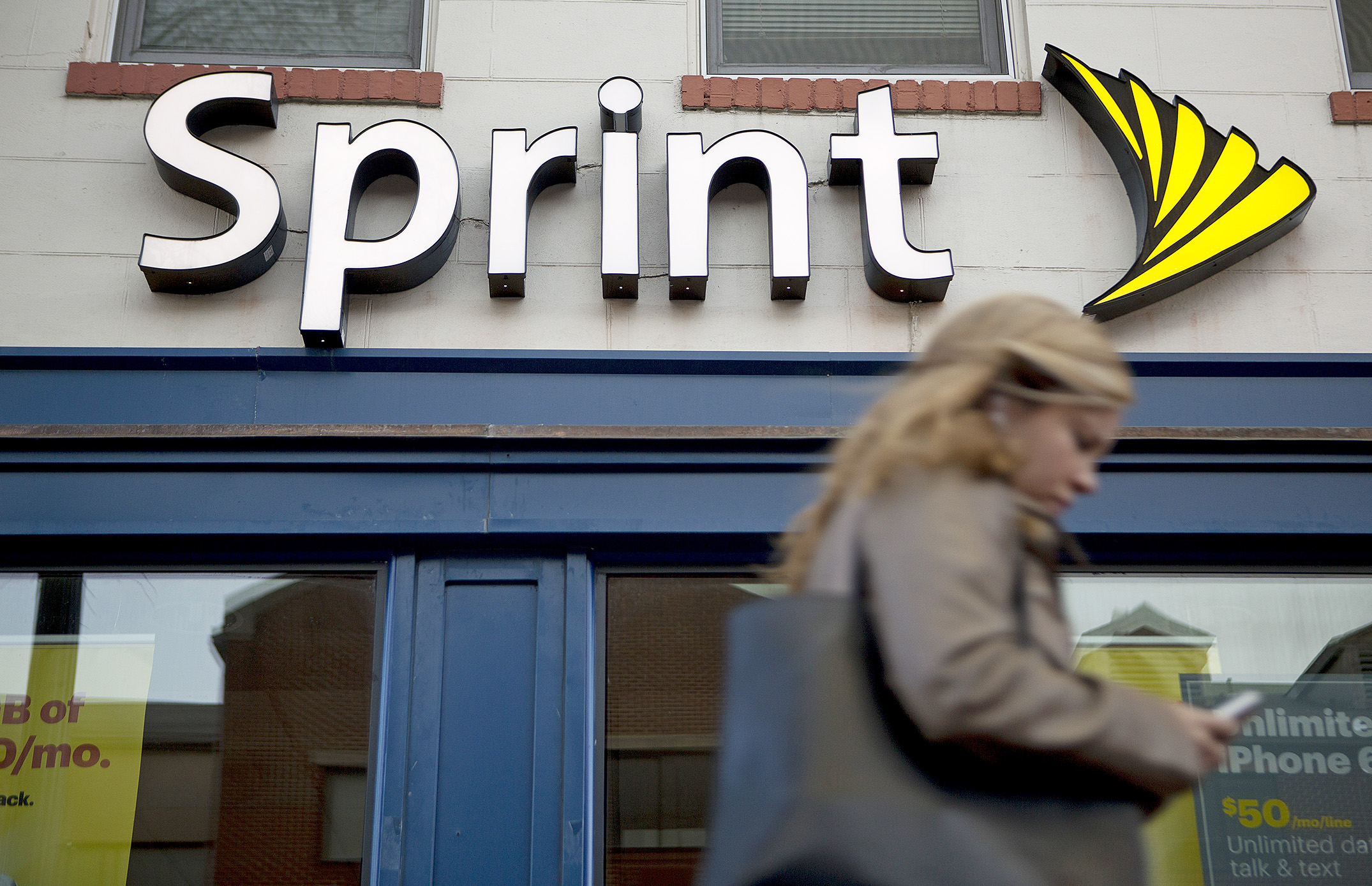 A pedestrian uses a mobile device while walking past a Sprint Corp. store in Washington.