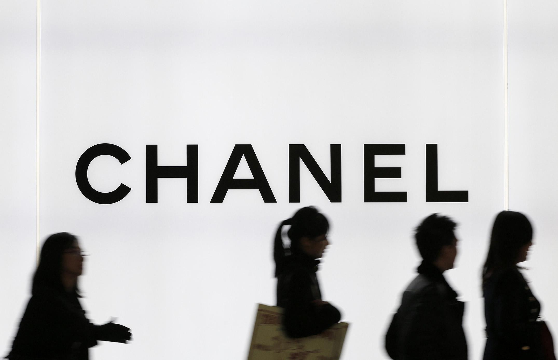 Pedestrians walk past signage for Chanel.