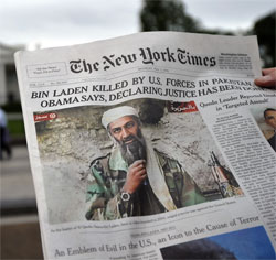 A man reads the front page of a newspaper featuring a picture of Al-Qaeda leader Osama bin Laden. Click image to expand.