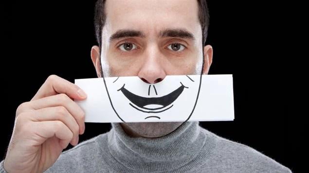 Un homme cache ses émotions derrière le dessin d'un sourire