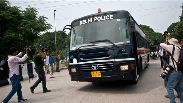 Les journalistes se pressent autour de l'autobus de la police indienne qui semble transporter les accusés.
