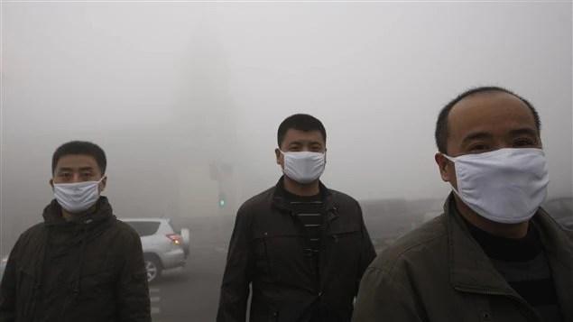 Des hommes marchent dans les rues de la capitale de la province du Heilongjiang, Harbin, paralysée par le smog.