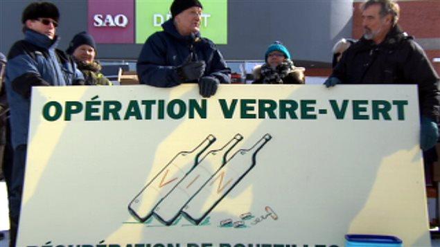 Photo : six personnes devant une succursale SAQ avec un carton géant Opération Verre-Vert. Dessin de bouteilles de vin.