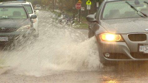Des voitures traversent une portion de route inondée en projetant un rideau d'eau.