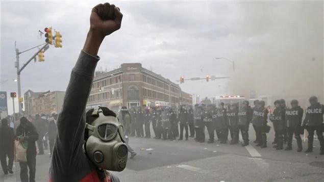 Les policiers et un manifestant avec un masque à gaz